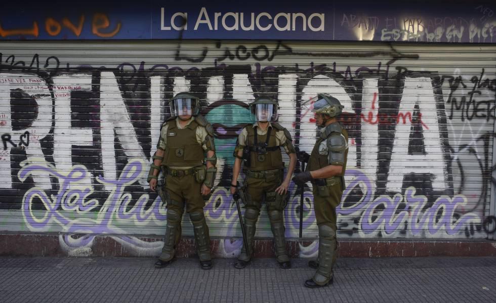Policiais chilenos fazem a segurança de um supermercado fechado pelos protestos em Santiago.