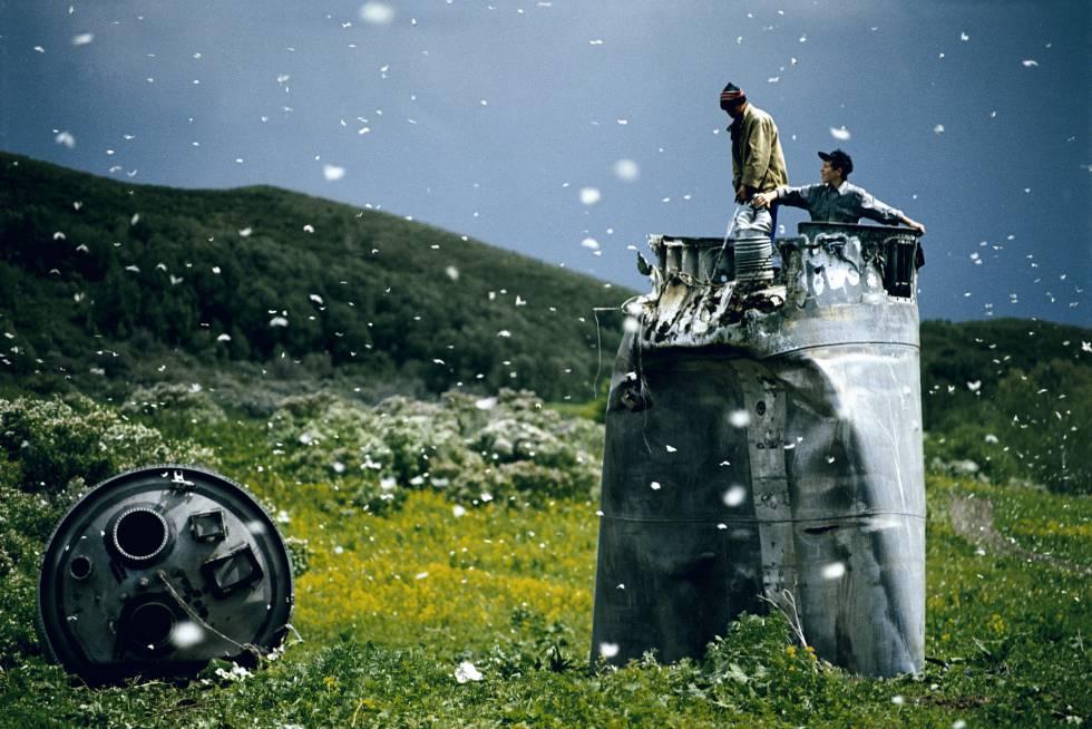 Aldeões recolhendo restos de um foguete espacial rodeados de mariposas, na República de Altai, Rússia, em 2000