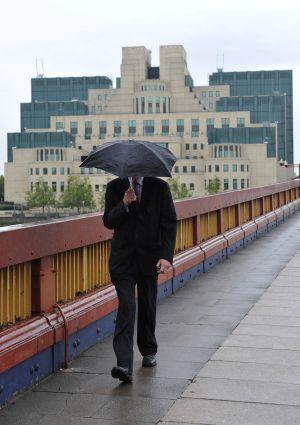 Homem caminha junto à sede do MI6 em Londres.