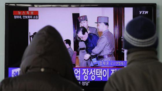 Dois sul-coreanos veem a notícia na televisão.