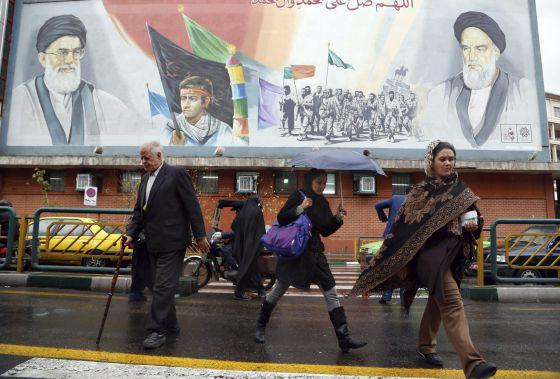 Pedestres passam por outdoor do líder supremo iraniano.