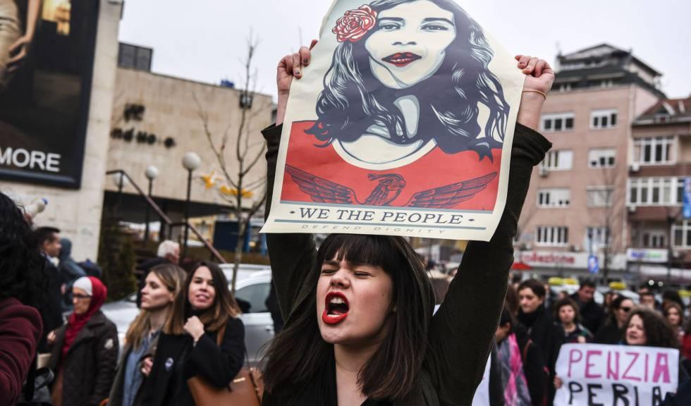 """Mulher com um cartaz que diz """"Nós, o povo, defendemos a dignidade"""", durante manifestação em Kosovo em março."""