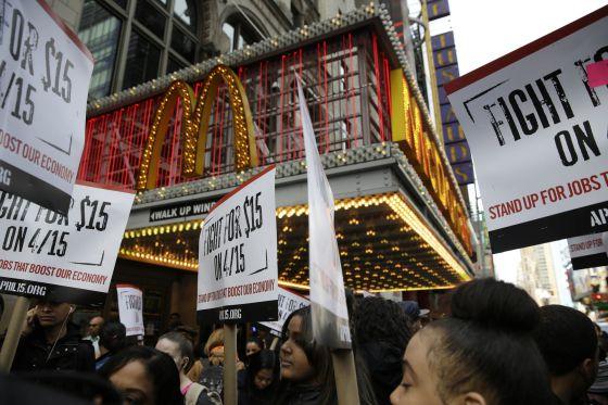 Trabalhadores do McDonald's reclamam salários mais altos diante de um restaurante da rede em Nova York.