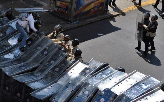 Um manifestante pula sobre os escudos da polícia.