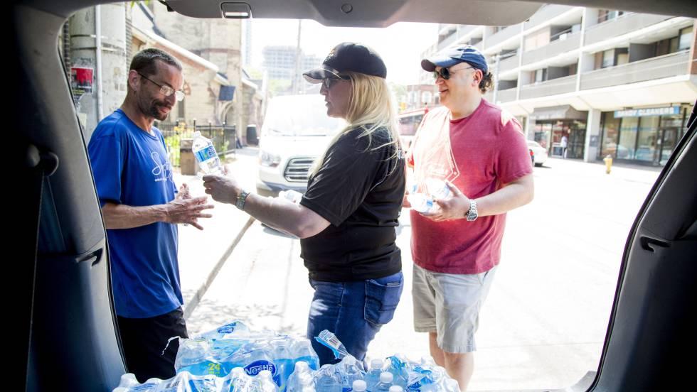 Uma mulher distribui garrafas de água em Toronto, no dia 30 de junho, durante a onda de calor no leste Canadá.