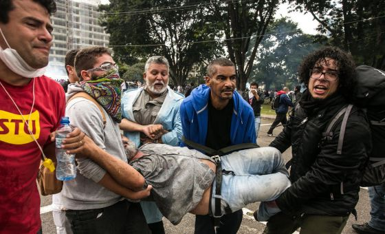 Manifestante é carregado por colegas durante protesto.