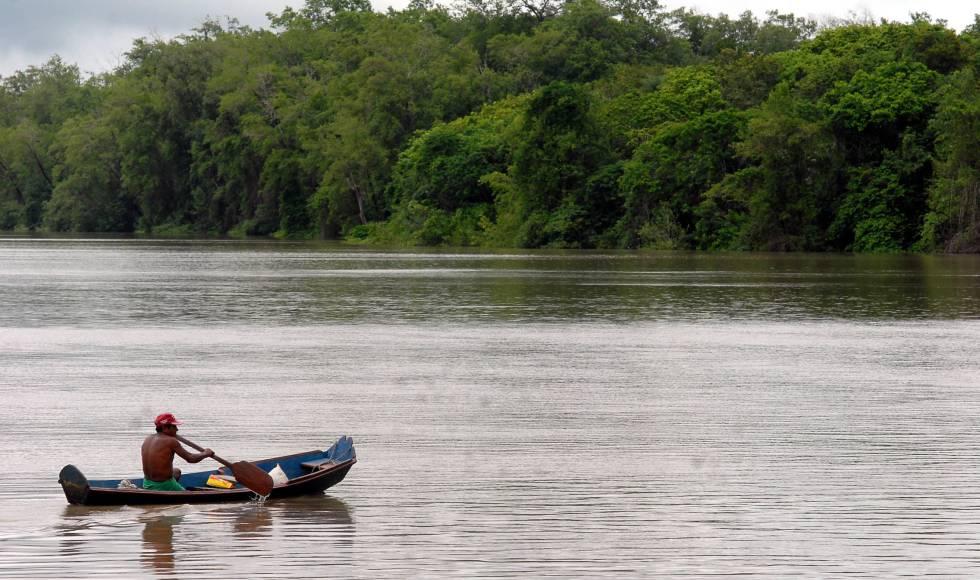 Homem rema em uma balsa na Amazônia brasileira.