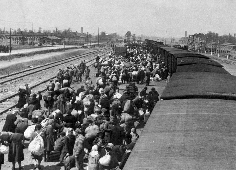 """Tirada de cima do trem, a fotografia mostra um panorama da plataforma de chegada a Birkenau, que fazia parte do complexo de Auschwitz. Ao fundo, é possível ver os crematórios II e III com suas chaminés. Os guardas da SS Ernst Hofmann e Bernhard Walter tiraram essas fotos em maio de 1944, no momento mais atroz do campo de extermínio nazista. A sobrevivente Lilly Jacob-Zelmanovic Meier encontrou as imagens por acaso e descobriu que seus vizinhos e familiares apareciam nelas, pouco antes de serem assassinados. Não se sabe porque as fotos foram tiradas. O """"Álbum de Auschwitz"""", como é chamado o conjunto de 193 fotos, é um documento único dentro do Holocausto e se encontra no Museu Yad Vashem de Jerusalém."""