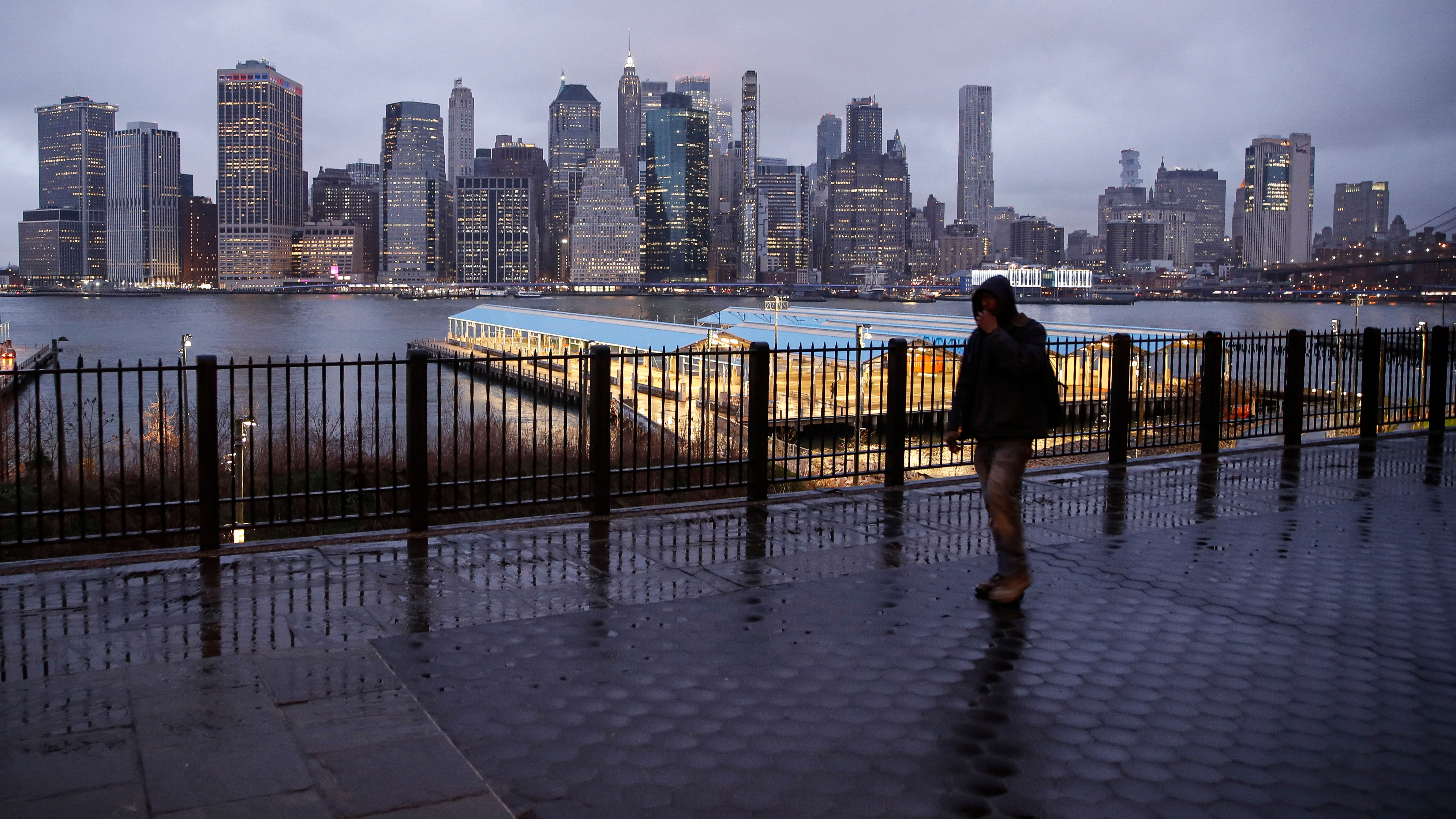 A person walks on an empty sidewalk as rain clouds hang over the downtown Manhattan skyline, Tuesday, March 17, 2020, in New York.  (AP Photo/John Minchillo)
