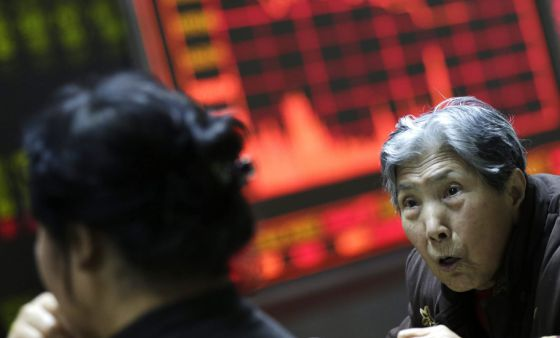 Vários investidores observam a informação bursátil em um escritório de corretaje em Pequim