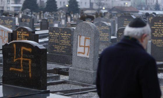 O líder de uma comunidade judaica examina tumbas pintadas com suásticas em um cemitério perto de Estrasburgo, em 2010.
