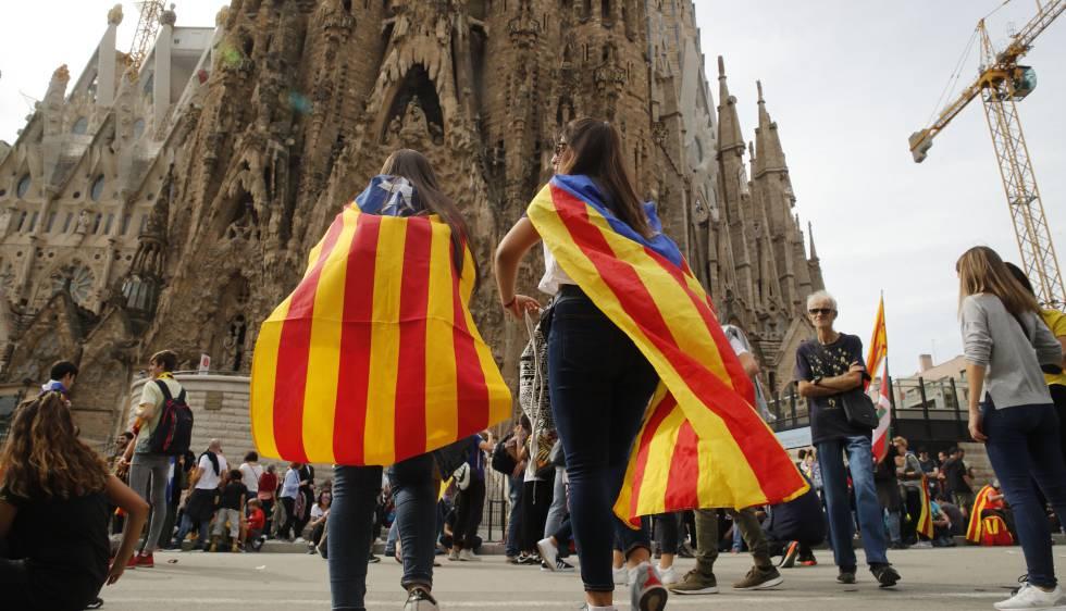 Jovens observam o fechamento do acesso principal da Sagrada Família em Barcelona.