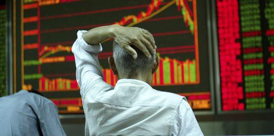 Um investidor revisa tela com informações da bolsa de valores em Pequim.