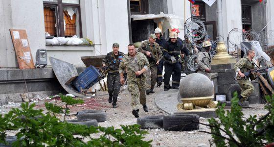 Pró-russos e bombeiros se afastam da sede regional de Donetsk.