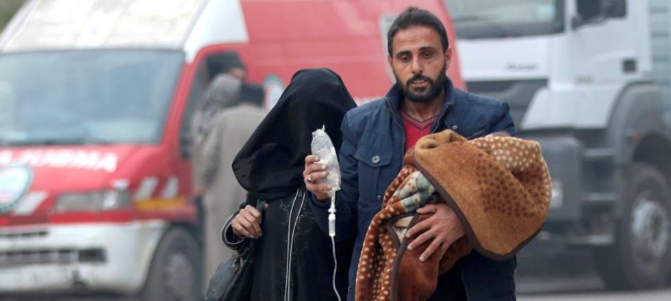 Homem evacua criança doente no leste de Aleppo