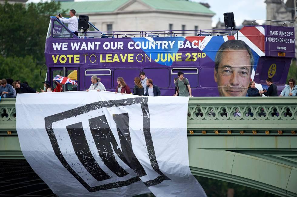Um ônibus com propaganda em favor da saída da UE passa por trás de partidários da permanência.