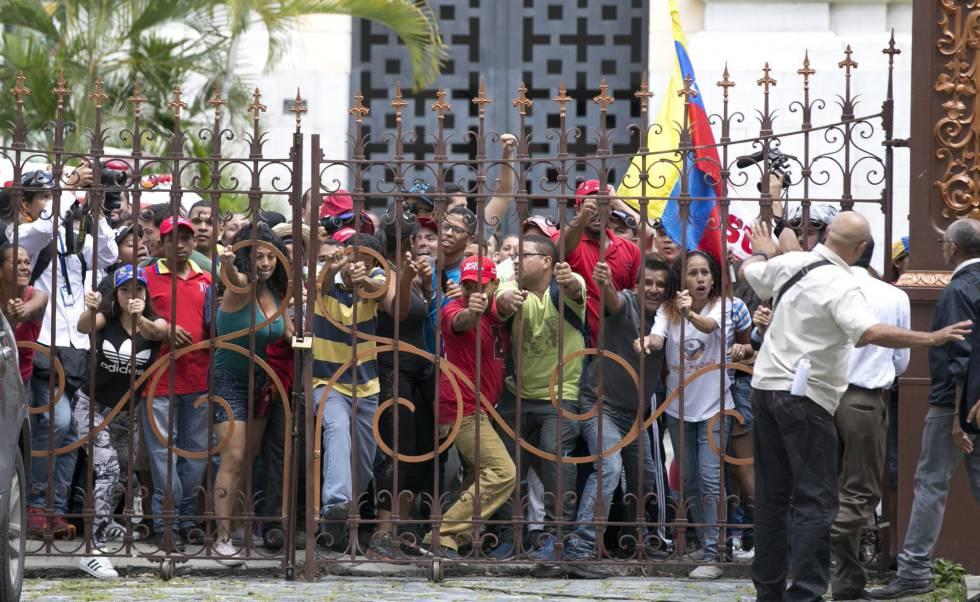 Venezuelanos que apoiam o Governo forçam a entrada no Parlamento, em Caracas.