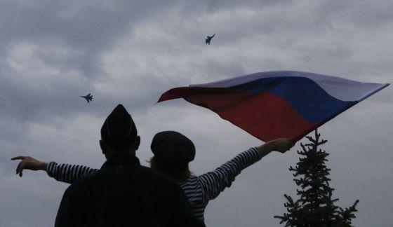 Uma mulher hasteia uma bandeira russa em Sebastopol.