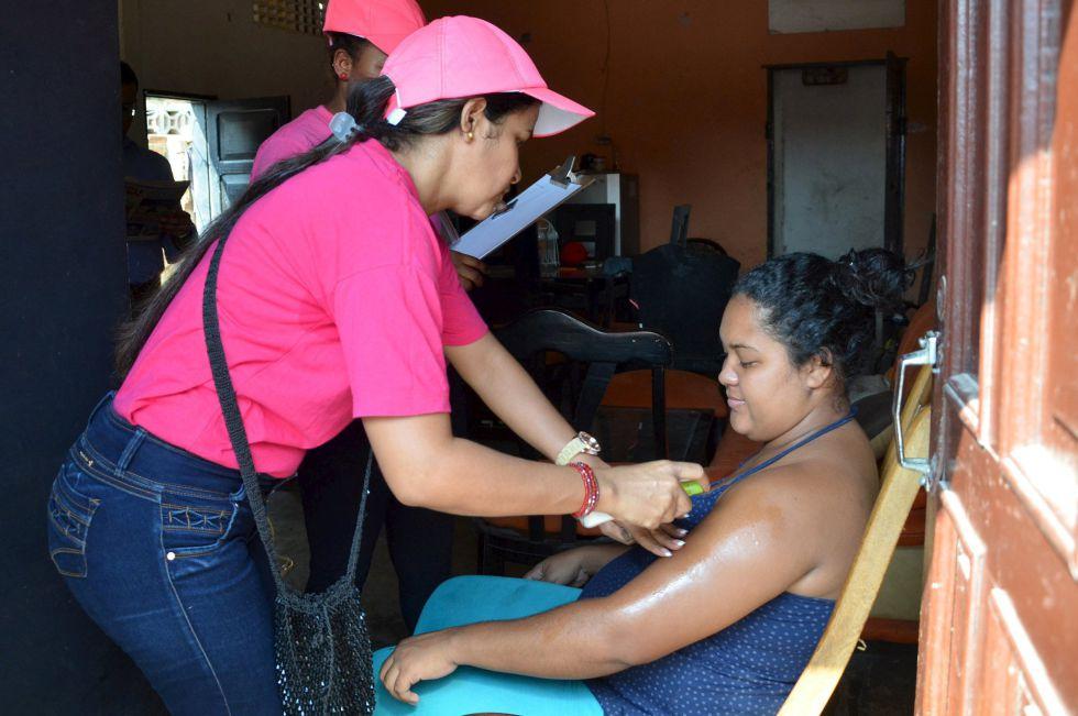 Profissionais de saúde ensinam uma mulher grávida a passar repelente contra o zika vírus em Barranquilla (Colônbia).