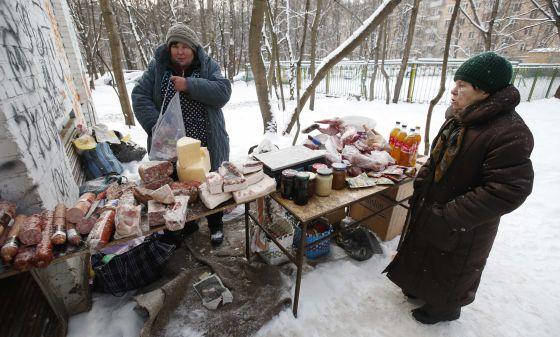 Mulher diante de um comércio de rua em Moscou.