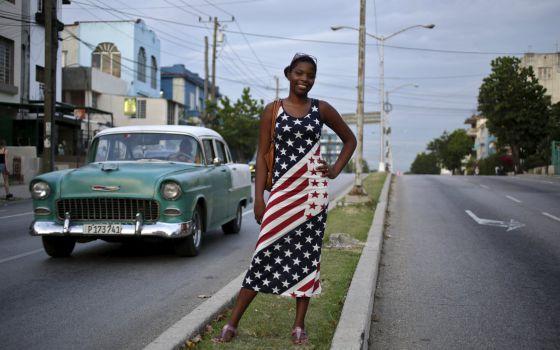 Jovem cubana vestida com a bandeira norte-americana em Havana.