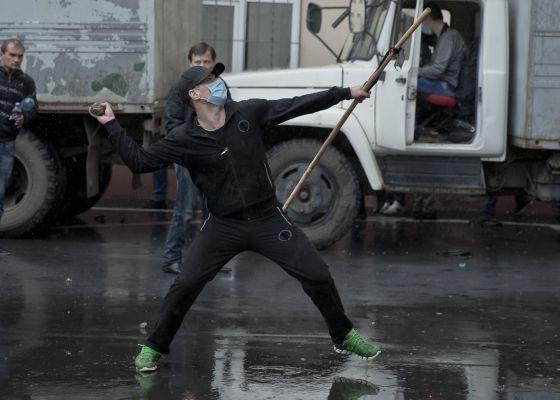 Manifestante pró-russo atira pedra em delegacia de polícia.