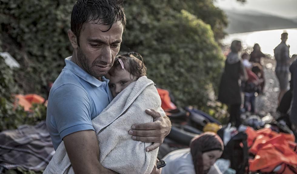 Um homem abraça e seca sua filha ao desembarcarem na ilha de Lesbos, após atravessarem parte do mar Egeu num bote de plástico.