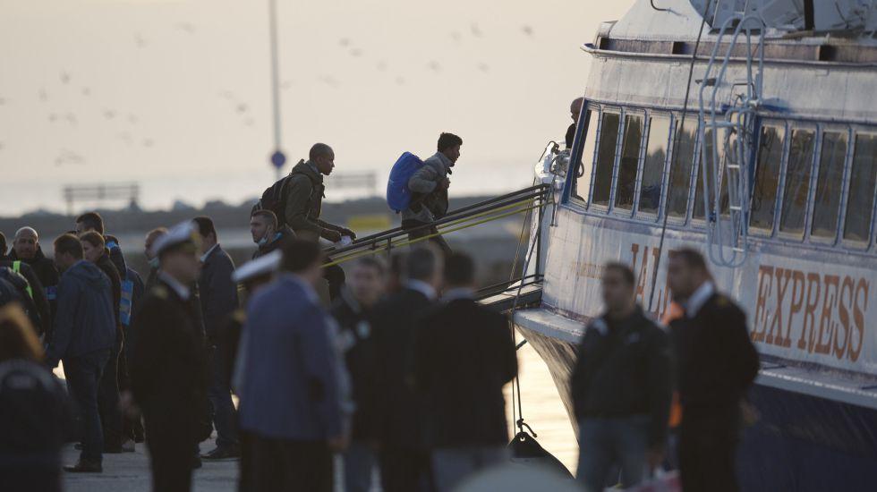Imigrantes sobem em um ferry em Mytilini, Lesbos, a caminho da Turquia.