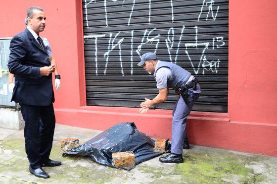 Policiais ao lado de partes de um corpo achado em São Paulo.