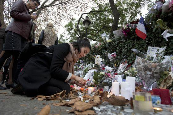 Uma mulher acende uma vela em frente ao Bataclan em Paris.
