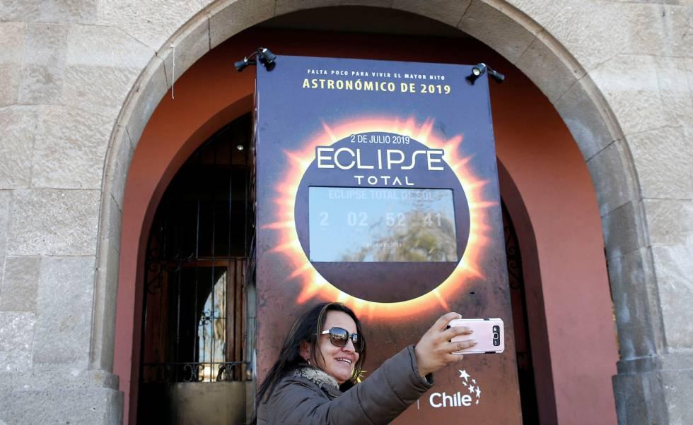 Turista faz selfie em frente a um mostrador com a contagem regressiva para o eclipse solar em Coquimbo (Chile).