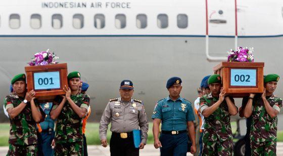 Militares transportam corpos de vítimas do voo QZ8501.