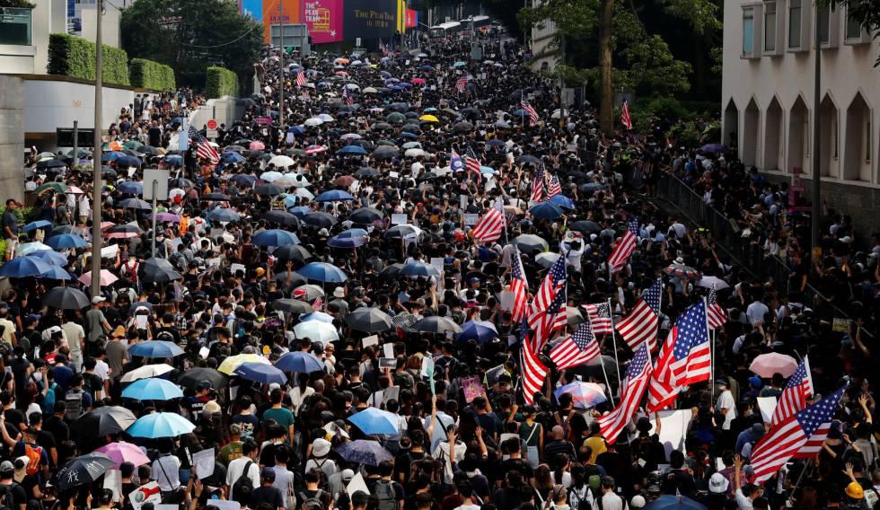 Os manifestantes levam guarda-chuvas e a bandeira dos EUA, no domingo, em Hong Kong.