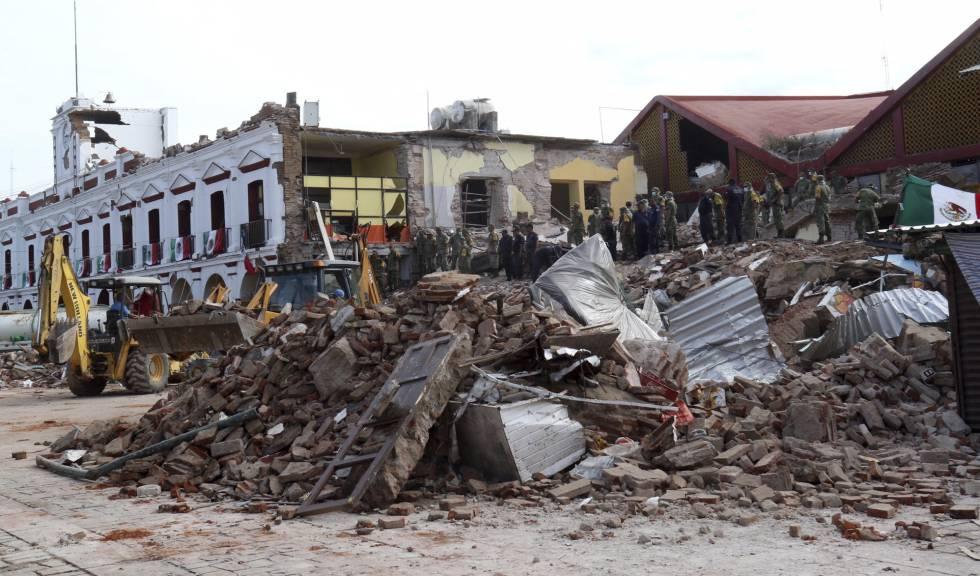 Bombeiros olham o que sobrou de um prédio municipal em Juchitan.