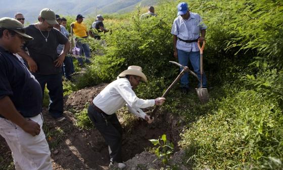 Um homem cava em uma fossa em busca dos estudantes desaparecidos. / SAÚL RUIZ
