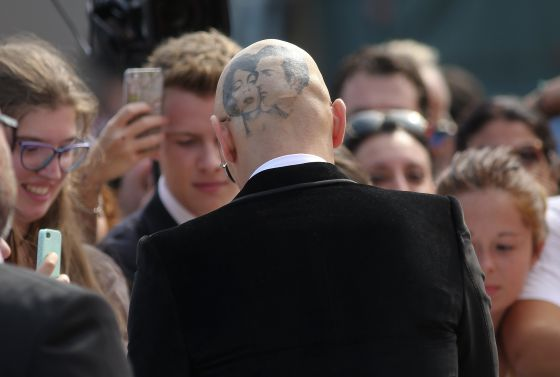 James Franco, de costas e com a cabeça raspada, concede autógrafos no festival de Veneza.