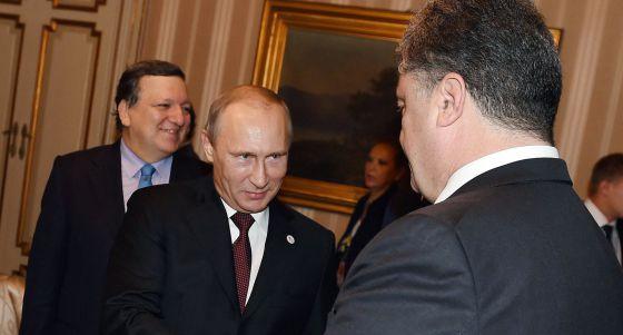 Putin cumprimenta seu homólogo ucraniano, Petro Poroshenko.