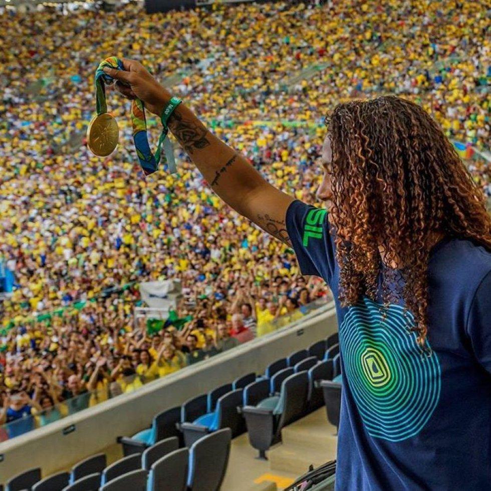 Rafaela Silva mostra sua medalha de ouro para os espectadores da partida entre a seleção feminina de futebol e Suécia.