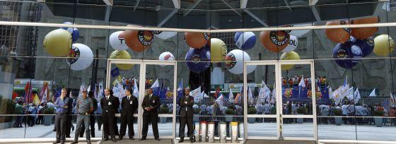 Seguranças observam protesto de sindicalistas contra mudanças nas leis trabalhistas.