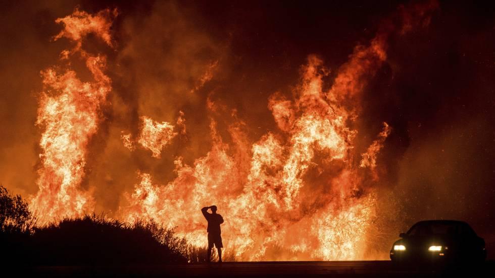 Um homem observa desde a estrada o incêndio de Ventura, Califórnia, na quinta-feira.