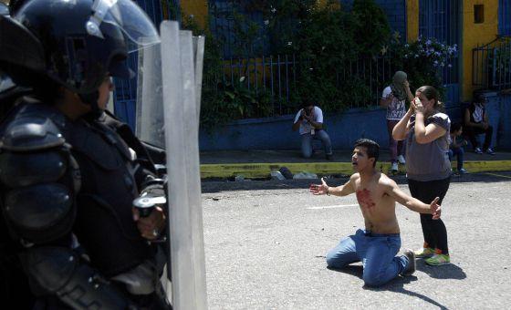 Jovem se ajoelha diante de policiais após morte de colega.
