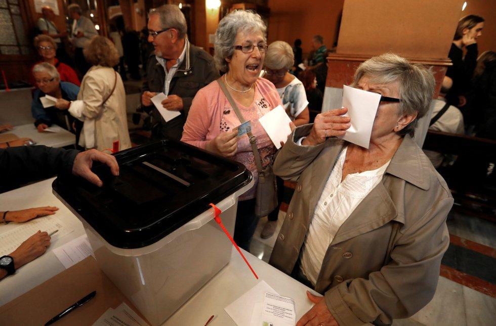Uma mulher beija sua cédula antes de colocá-la na urna.