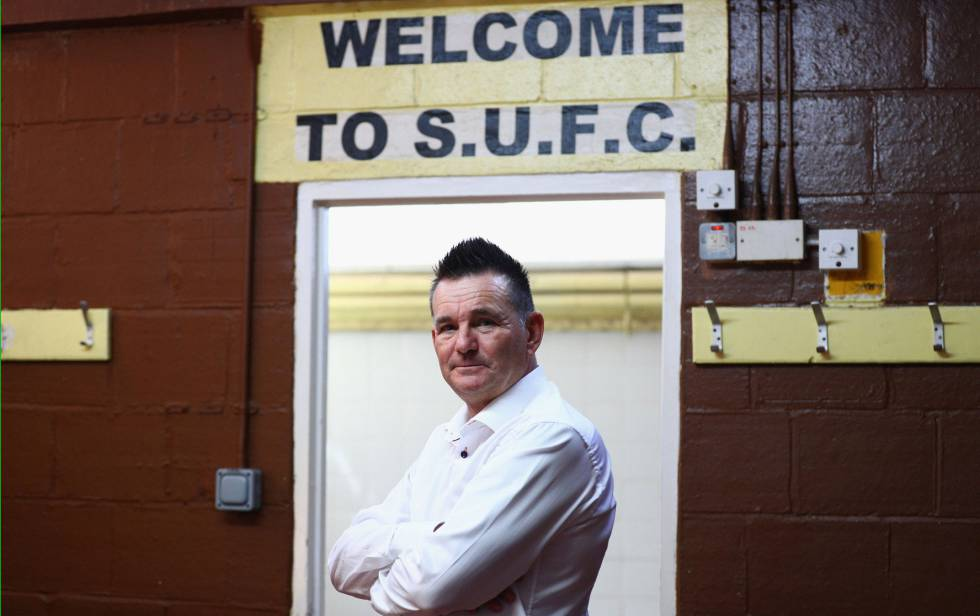 Paul Doswell, técnico do Sutton United, posa na entrada do campo.