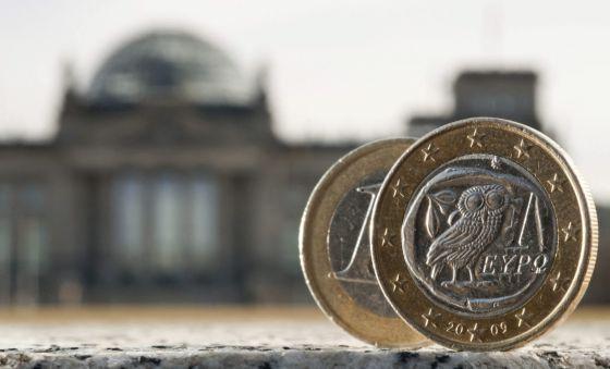 Duas moedas de um euro, uma delas cunhada na Grécia, fotografadas diante do parlamento alemão, em Berlim.