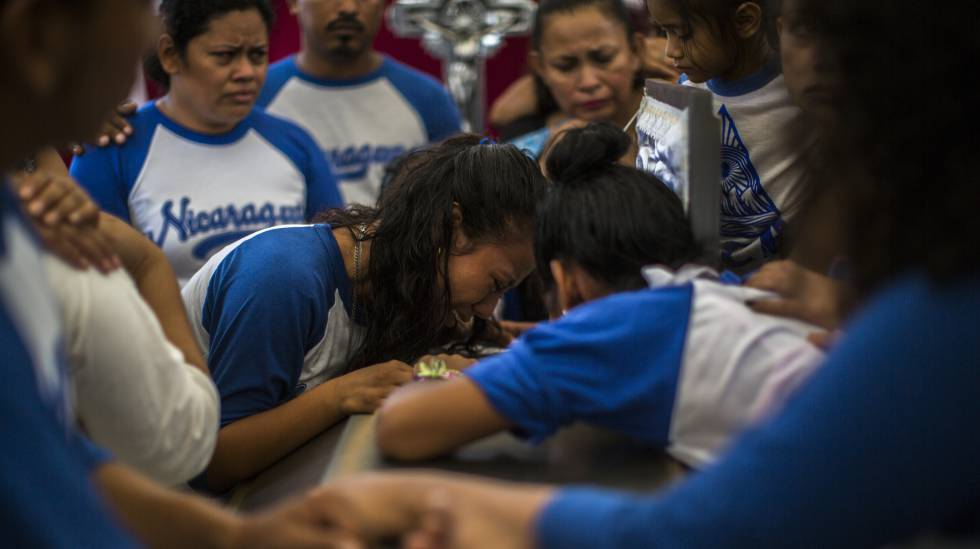 Amigos de Gerald Vásquez choram sobre seu caixão durante o funeral do jovem de 20 anos.