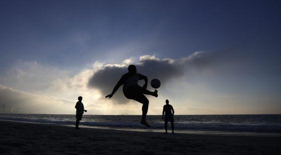 Homens jogam futebol na praia de Copacabana.