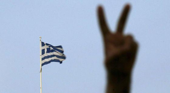Partidário do não faz o gesto da vitória, hoje em Atenas.