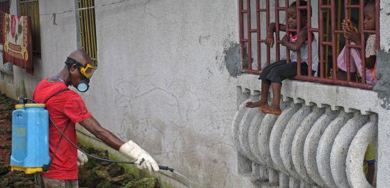 Um trabalhador desinfeta uma casa em Monróvia (Libéria).