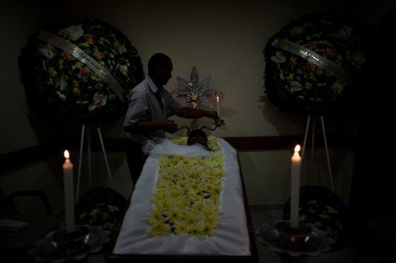 Motorista da Prefeitura enfeita um cadáver antes do enterro.