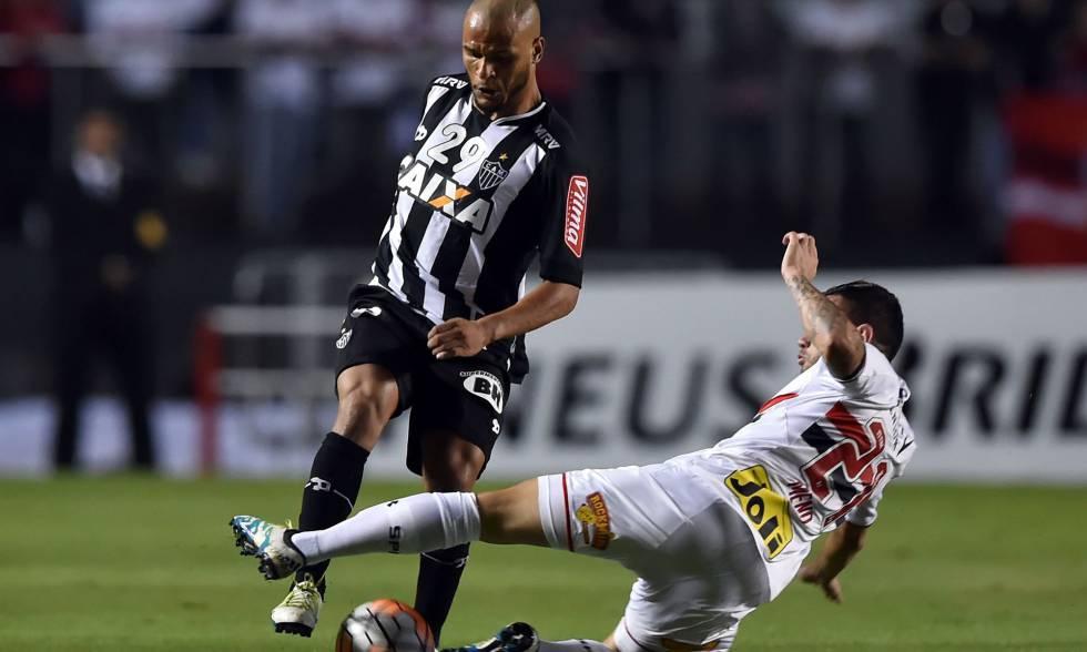 Patric (esq.) disputa a bola com Mena.